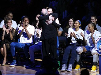 Mike Thibault - Wearing a University of Minnesota tie, Thibault hugs Lindsay Whalen at her retirement in 2018