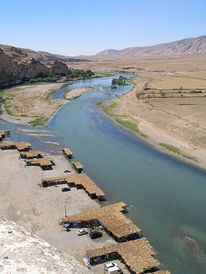 Hasankeyf - View of the Tigris River in Hasankeyf, seen from the Citadel. Reed covered restaurants serve fresh river fish along other regional specialties
