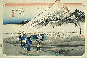 Three gathers walking away from Mount fuji. There looks like there is a animal behind them in the background.