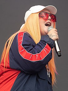 A woman is singing into a hand-held microphone with her eyes partly closed. The back of her right hand has an obscured image or a tattoo. She wears a white cap and rose-coloured glasses. Her hair is strawberry blonde and hangs down past her shoulders. She wears a red and blue jacket.