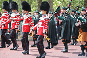Irish in the British Armed Forces - Irish Guards Pipers at Trooping the Colour. The bagpipers are wearing saffron kilts and brogues, as well as a caubeen headdress.