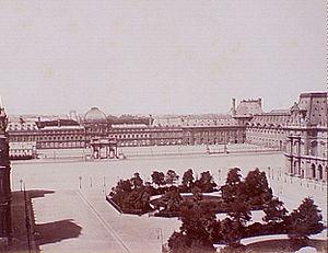 Άποψη από την αυλή του Λούβρου απ' όπου φαίνεται η ένωση του Λούβρου (σε πρώτο πλάνο) και του Ανακτόρου του Κεραμεικού (σε δεύτερο πλάνο), που τώρα είναι ένας μεγάλος κενός χώρος. - Η πυραμίδα του Ιέο Μινγκ Πέι βρίσκεται σήμερα στο πρώτο πλάνο, στη θέση της συστάδας των δέντρων.