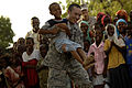 U.S. Air Force Senior Airman Patrick Brush, a trumpet player from the U.S. Air Force Central Band called Falcon, picks up a small boy and starts dancing during a concert at Dammerdjog, Djibouti, May 21, 2008 080521-F-JQ435-148.jpg
