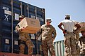 U.S. Navy Petty Officer 2nd Class Markus Guinn, left, with Combined Joint Interagency Task Force 435, carries boxes of donated items to be stored for future distribution by the Operation Outreach Afghanistan 130728-D-BO405-050.jpg