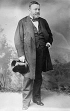 Grant is standing in a civilian dress suit holding a top hat after the Civil War.