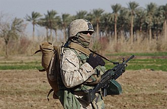 United States Marine Corps - Machine gunner from 1st Platoon, Company B, 1st Battalion, 23rd Marine Regiment in cold weather gear armed with a Squad Automatic Weapon taking part in a security patrol around Ramadi, Iraq, 27 December 2006.