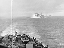Black and white photo with part of a ship in the foreground and flames and smoke risking from the left of a warship in the background. Several other ships are visible on the horizon at the rear of the photo.