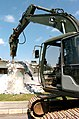 US Navy 050309-N-9712C-002 Equipment Operator 1st Class Jason Morris uses an excavator with a hydraulic rock hammer attachment to tear down the vehicle dispatch office on Camp Shields, Okinawa.jpg