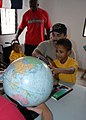 US Navy 070912-N-9486C-001 Chief Warrant Officer Dan Trevino, chief engineer aboard High Speed Vessel (HSV 2) Swift, shows one of the children at Jackie's House Orphanage where he's from.jpg