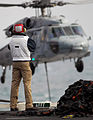 US Navy 080115-N-2984R-284 A crewmember assigned to the Nimitz-class nuclear powered aircraft carrier USS Harry S. Truman (CVN 75), observes an MH-60S Seahawk helicopter as it performs a vertical replenishment.jpg