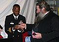 US Navy 090303-N-6764G-113 Bishop Polykarpos presents a gift to Cmdr. Eric Cash, commanding officer of the amphibious transport dock ship USS San Antonio (LPD 17), during a reception for visitors from Santorini, Greece.jpg