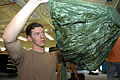 US Navy 090327-N-5366K-018 Aircrew Survival Equipmentman 2nd Class Christopher Allen inspects a reserve pilot parachute for holes and tears.jpg