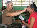 US Navy 090402-N-1580K-690 Navy optometrist Cmdr. Louis Perez adjusts a new set of reading glasses on 71-year old villager Marcelina Martinez during the Beyond the Horizon humanitarian assistance exercise in Honduras.jpg