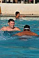 US Navy 100515-N-8433N-338 Builder 2nd Class Carle Spragle encourages a Special Olympics Guam athlete working on his breaststroke at the Hagatna swimming pool in Guam.jpg