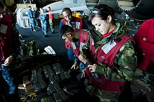 US Navy 111213-N-BT887-199 Aviation Ordnanceman 3rd Class Alexis Johnson, from Omaha, Neb., loads rounds into a magazine for small-arms qualificati.jpg