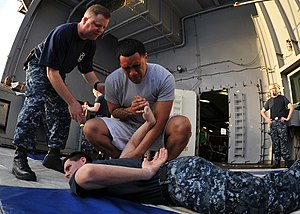 US Navy 111229-N-YB753-101 Machinist's Mate Fireman Apprentice Peni Lemusu demonstrates a control hold on Information Systems Technician 3rd Class.jpg