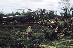 A group of Marines carry a wounded Marine to a helicopter.