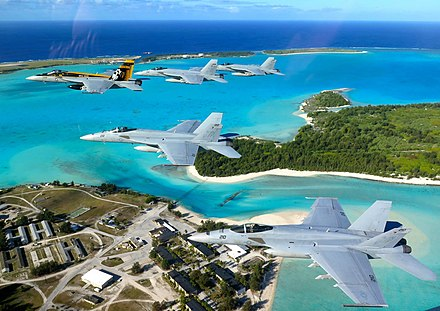 "The VFA-27 Royal Maces, a United States Navy F/A-18E Super Hornet squadron based in Atsugi, Japan, flies over the ""Downtown"" area of Wake Island. VFA-27 Wake Island.jpg"