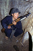 A Vietcong soldier wearing typical clothing and sandals in a tunnel.  They often ate and slept in these tunnels and would disappear into them when the Americans raided a village.