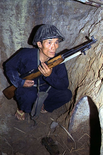 Viet Cong soldier crouches in a bunker with an SKS rifle Vietcong1968.jpg
