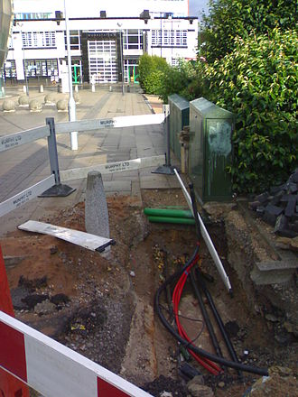 Television in the United Kingdom - A pavement dug up revealing the cables underneath. The green box is a common sight in areas with cable coverage, as are manhole covers inscribed with CATV.