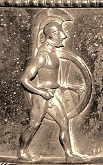 Relief of a soldier in profile, wearing a crested helmet and carrying a circular shield