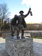 A memorial statue showing two men, a miner in difficulty, and a rescuer helping for half carry him. The statue if on a stone plinth.