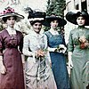 Four women in Edwardian dresses, each a different colour