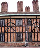 Eine Nahaufnahme eines Gebäudes aus schwarzen Balken und rotem Backstein.  Das Gebäude hat vier hohe, gemauerte Schornsteine.  In der Mitte des Gebäudes verläuft ein relativ modernes Abflussrohr.