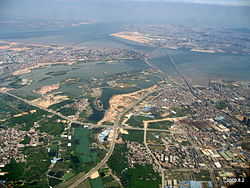 An aerial view of Jimei District (foreground and center), connected by numerous bridges with Xiamen Island's Huli District (in the background right, including Xiamen Gaoqi International Airport).