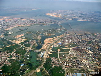 Jimei District - An aerial view of Jimei District (foreground and center), connected by numerous bridges with Xiamen Island's Huli District (in the background right, including Xiamen Gaoqi International Airport).