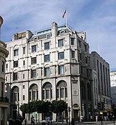 Um edifício de Edwardian com seis andares fica em um dia moderada, uma bandeira voando em cima dele.