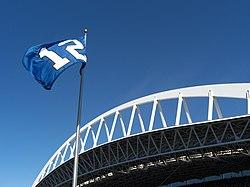 Una bandiera blu con un bianco numero 12 vola contro un cielo sereno.  Un ampio capriata bianco è dietro il pennone.