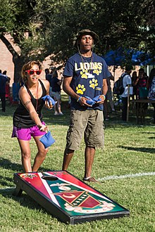 A woman tossing a cornhole bag in front of her board while a man stands beside her