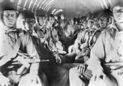 Men with helmets sit in an aircraft with weapons held across their chests, strapped into parachutes