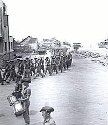 Soldiers marching under arms with rifles at the slope file past a drum band