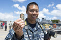 A U.S. Sailor holds up a coin given to him by the Chairman of the Joint Chiefs of Staff Army Gen. Martin E. Dempsey after a tour of the fast attack submarine USS North Carolina (SSN 777) in Pearl Harbor, Hawaii 140630-D-KC128-416.jpg