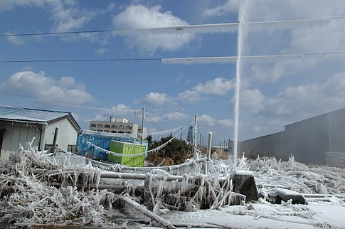 A damaged water pipe shoots into the air after the tsunami. Image: U.S. Navy.