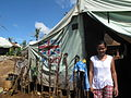 A woman stands in front of a tent supplied by UK aid near Guiuan in the Philippines (14133457721).jpg