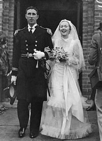 A young couple in wedding attire walking outside of a building. The man is on the left, and is dressed in ceremonial naval attire. He is holding a hat in his right hand down by his side. The bride is in a white gown with a veil. She is smiling and carrying a bouquet of flowers