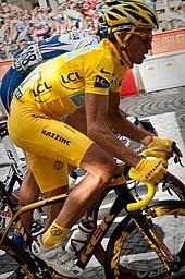 Een man in gele kleren, ontmoette Een gele helm en gele Werkhandschoenen, rijdend op Een fiets.  Vlak achter zoom is Een andere fietser, in blauwe kleren.