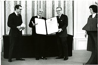 Ernest Ambler - Ernest Ambler is presented with the medal and diploma of the President's Award for Distinguished Federal Civilian Service in 1977.