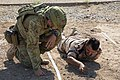 Australian soldier teaching an Iraqi soldier how to uncover IEDs in April 2018.jpg
