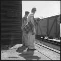 Bakersfield, California. On the Freights. Two Oklahoma boys headed back home standing on the edge of a flat waiting... - NARA - 532067.tif