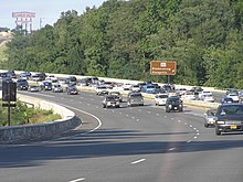 A tree lined six lane freeway with congestion on the right side of the road surrounded by trees. To the right, a brown sign reads Maryland Route 450 Bladensburg Annapolis with an arrow pointing to the upper right. A sign for the Capital Plaza Mall is in the distance