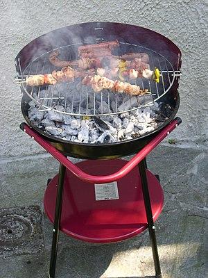 Italiano: Barbecue con spiedini e salciccia al...