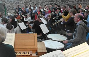 players of the Baroque orchestra L'arpa festante rehearsing with a choir, with part of the continuo organ's keyboard in the foreground, three players of natural trumpets standing on the right, the timpani player sitting between them and the organ, flauti traversi in the background