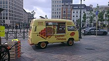 Sitting in a city square is a yellow van decorated with images of waffles and with serving window on the side