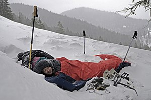 Bivouac shelter - A bivouac sack (in red) covering a man within a sleeping bag in Benediktenwand, Germany