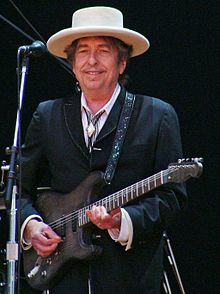 A gray-haired man wearing a hat plays a guitar.